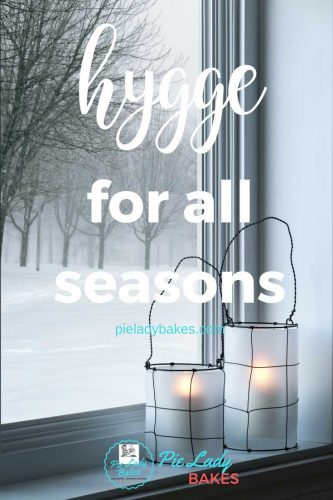 text says hygge for all seasons shows a winter snow storm outside and frosted white candles on the windowsill inside showing how to be cozy
