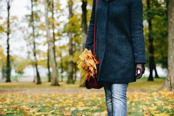 Fall outdoor scene, shows woman walking in a dark blue coat, blue jeans, brown leather gloves and red shoulder bag with a handful of leaves, image doesn't show woman's head.