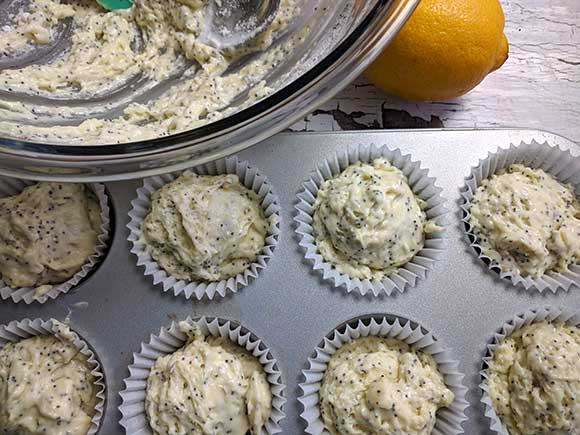 filling the muffin cups inside a muffin pan