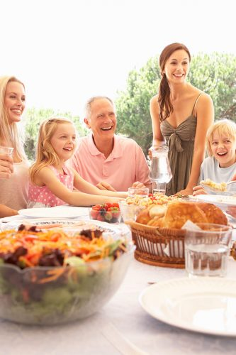 Family and friends looking at a distant object, with food, salads and bread on a table in the foreground