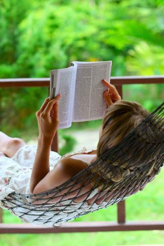 woman reading a book while lying in a string hammock with trees in the background