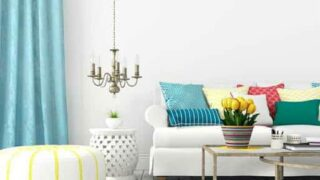 living room scene spring like clours of blue yellow red and green white sofa white ottoman blue curtains with lots of pillows and yellow tulips in a multi coloured planter on a glass table