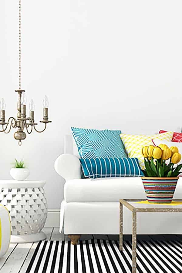 white sofa with colourful pillows, chandelier, and pot of yellow tulips all depicting how to live hygge in spring
