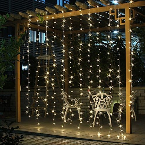 curtain of mini lights with white cast iron chairs behind on patio