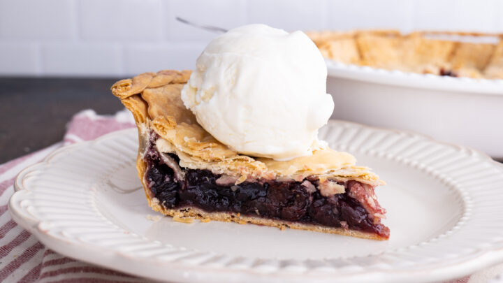 slice of homemade cherry pie on a white plate with a scoop of vanilla ice cream on top