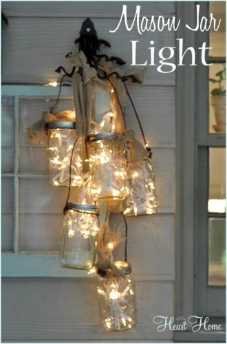 front door arrangement of mason jars with string lights inside hanging from a black iron hook on white siding