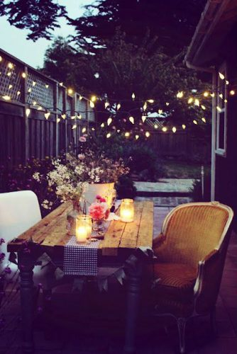 wooden backyard table with white chair and gold coloured chair, flowers and candles on table with patio lights strung from fence to back of house