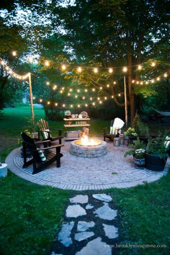 backyard fire pit with chairs place around it, stone path leads to conversation area, and several strands of string lights across entire area