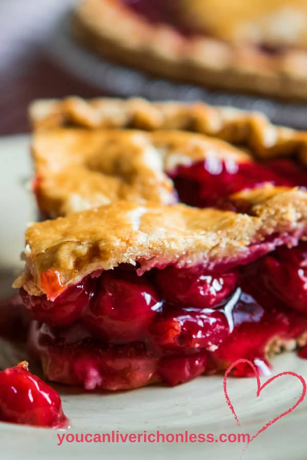 Large slice of cherry pie on a white plate shows rest of pie in the background