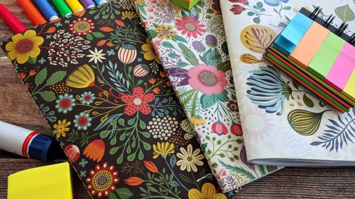 flowered pattern journals, dark and bright colours, post it tags, coloured markers and stickers on medium brown wooden table