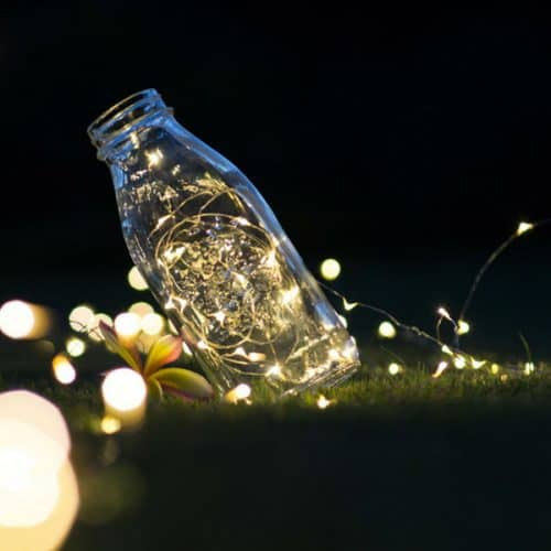 milk bottle with string fairy lights inside at night on green grass