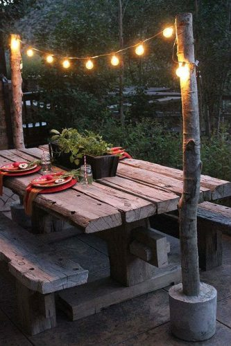 string lights are mini light bulbs strung between two tree posts and a wooden picnic table with plants and table settings
