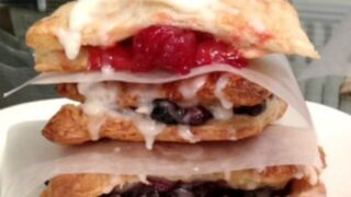 close up image of puff pastry cherry and blueberry pop tarts with white sugar glaze dripping down the sides