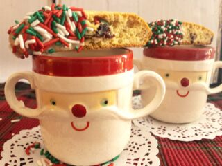 two santa clause face on mug with hot chocolate and cake mix biscotti with red green and white sprinkles on one end all on a white paper doily