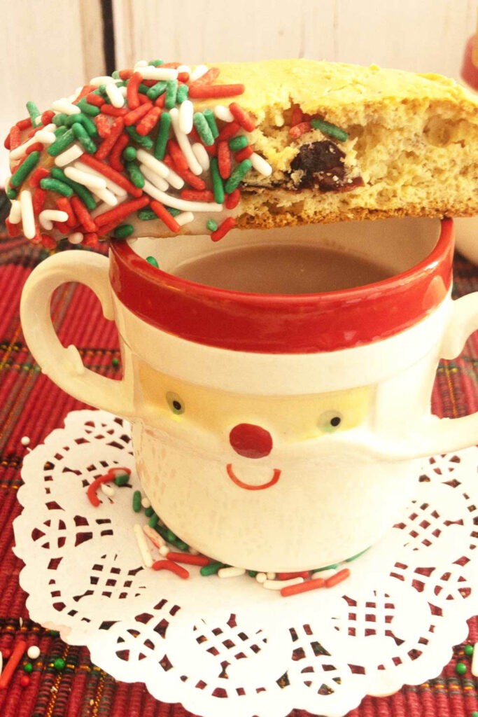 santa clause face on mug with hot chocolate and cake mix biscotti with red green and white sprinkles on one end all on a white paper doily