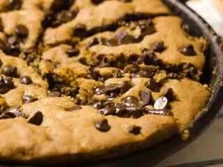 nutella stuffed skillet cookie closeup shows cast iron pan, cookie is sliced ready to eat