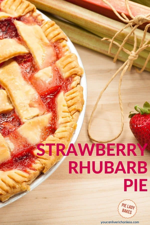 side view of strawberry rhubarb pie, a bunch of raw rhubarb ties with string and fresh strawberries to the side