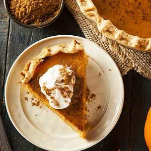 overhead shot of pumpkin pie with whipped cream and pumpkin pie spice on a white plate with fall decorations and corner of whole pumpkin pie showing in upper right corner