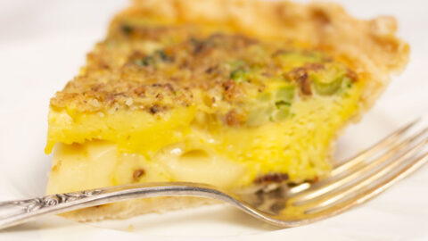 Slice of homemade broccoli quiche with fork on a white plate