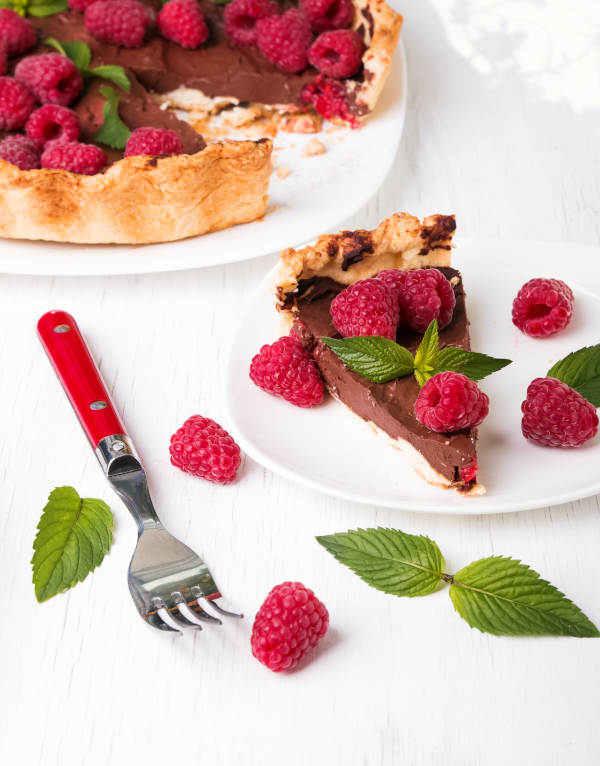 slice of chocolate raspberry tart on a white plate with whole tart in background red handle fork and mint leaves
