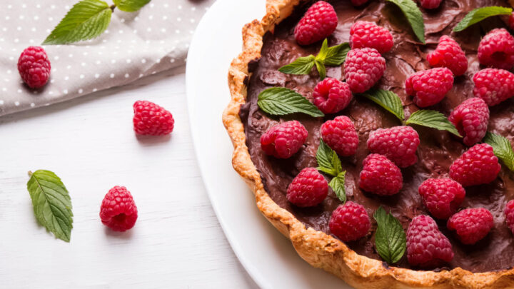 chocolate tart with raspberries on top with single raspberries and mint leaves and grey napkin