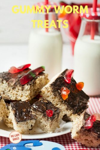 chocolate iced marshmallow treats, topped with gummy worms on a white plate, red and white checked cloth and two bottles of milk with straws in the background