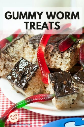 rice krispie treats with chocolate icing on a white plate with gummy worms on top, on a red and white checked cloth