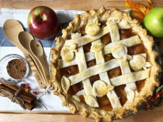 lattice topped apple pie with measuring spoons, cinnamon sticks, apples on a wooden board