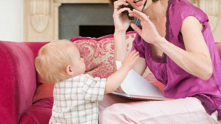 woman on phone with planner and pen in hand shows small child reaching out for her