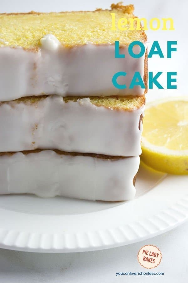 lemon loaf cake with white glaze icing, sliced on a white plate with lemons on the side,