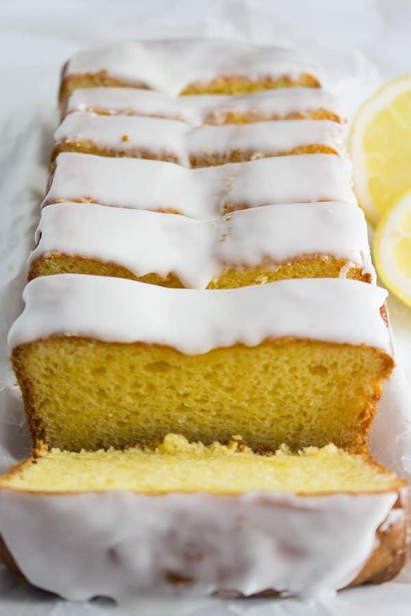 lemon loaf pound cake slices close up with lemon glaze frosting