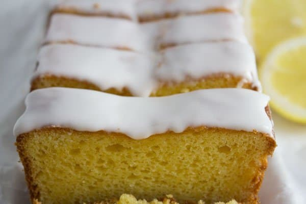 lemon loaf cake with white glaze icing, sliced on a white plate with lemons on the side, wording on top Lemon Loaf Cake