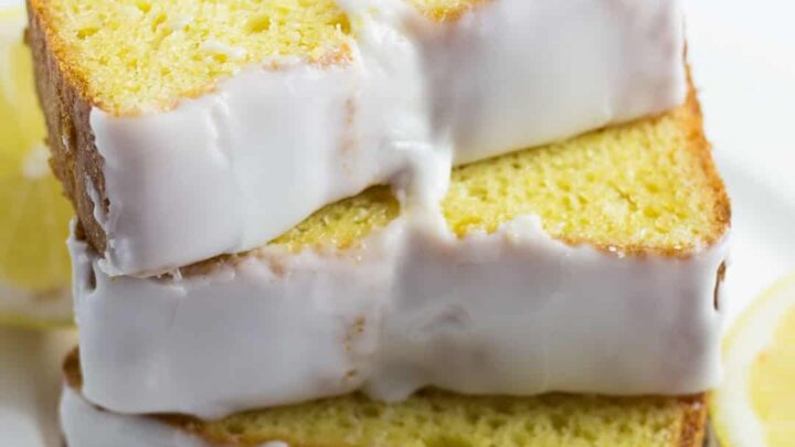 lemon loaf cake with white glaze icing, sliced on a white plate with lemons on the side,
