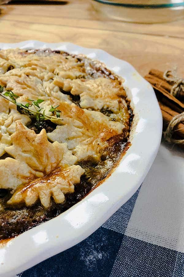 side view of tourtiere with pie crust maple leaves in a white baking dish and cinnamon sticks on the side.