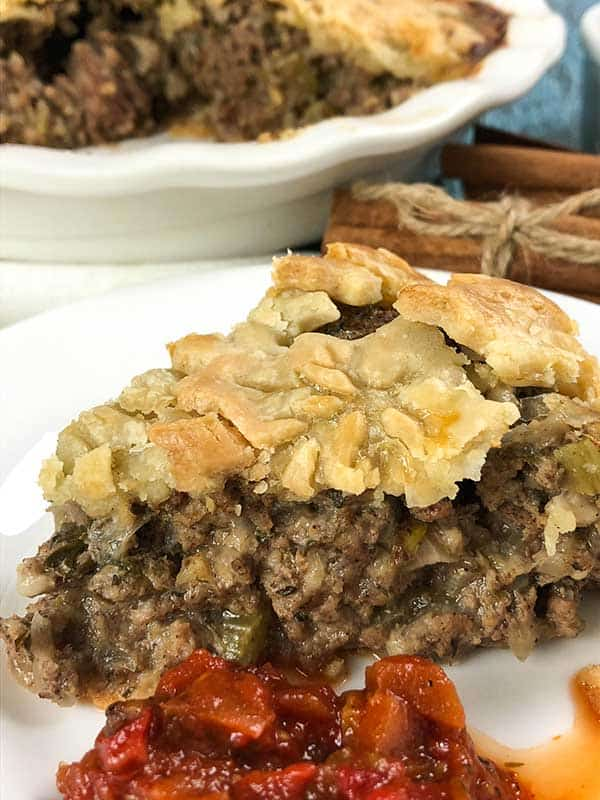 slice of tourtiere, with antipasto on a white plate