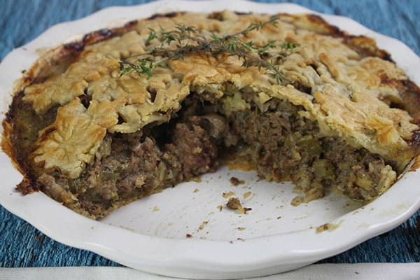 french canadian tourtiere with two servings removed in white baking dish