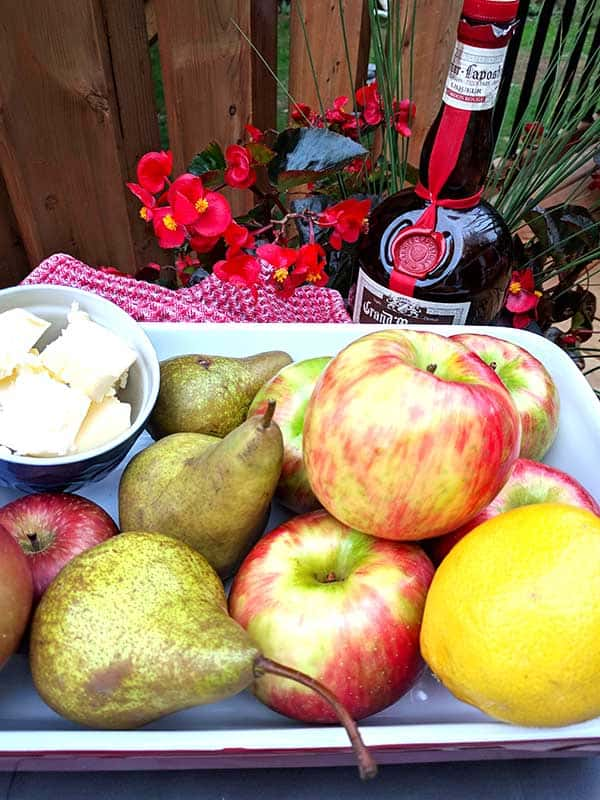 mom's delicious apple crisp getting ready to baked with butter, apples, pears, and dry ingredients in a green bowl with a red napkin and bottle of grand marnier
