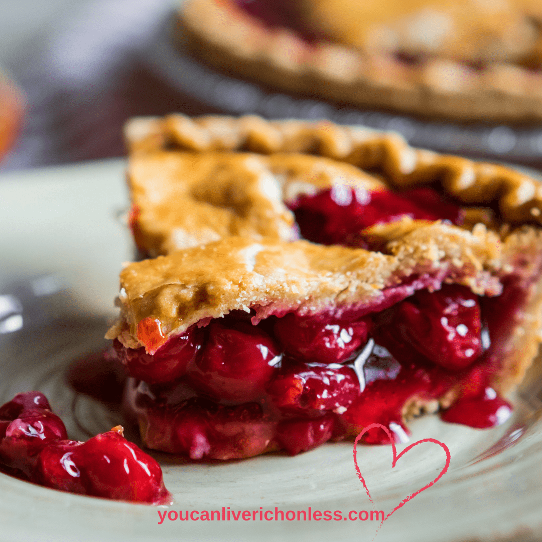 Closeup of slice of cherry pie on a white plate