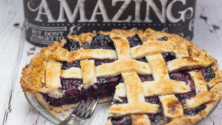 Razzleberry pie with a slice cut out, fork on top of pie in front of a black box with the word 'amazing' in white letters on it.