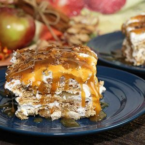 apple pie cheesecake lasagna slice on blue plate with apples in background