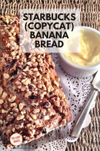 loaf of banana bread with crushed walnut and sugar topping on a white paper doily on a woven grass tray white ramekin of butter and silver knife on side