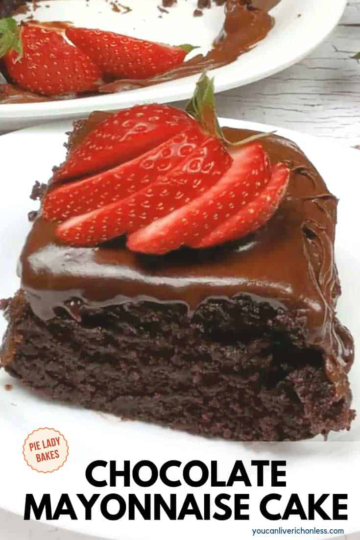 piece of chocolate mayonnaise cake on white plate with sliced strawberries on top