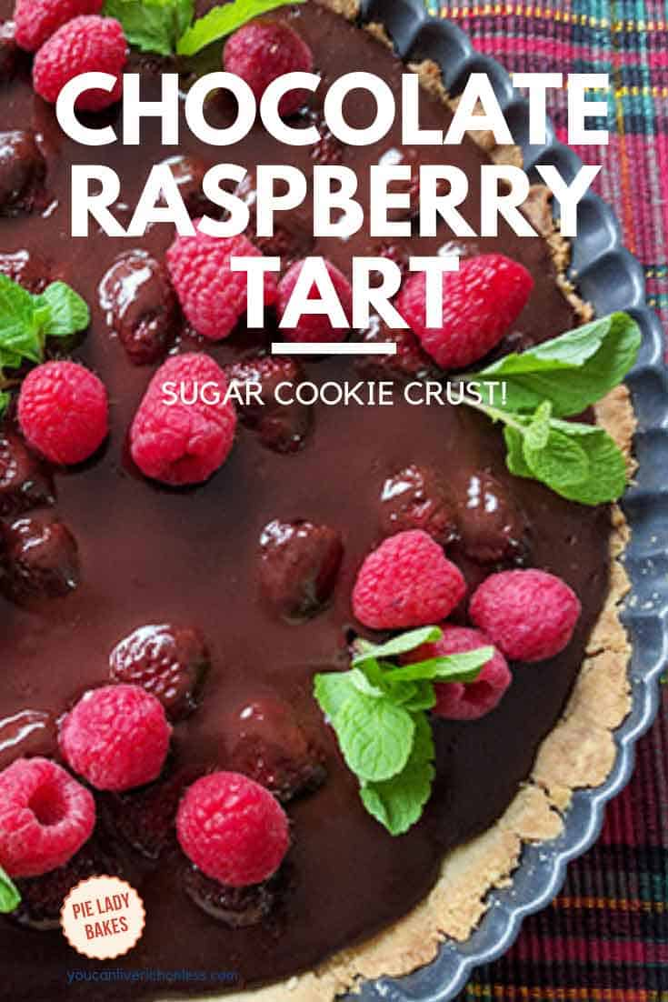 chocolate raspberry tart, part on tartan placemat with raspberries and fresh mint