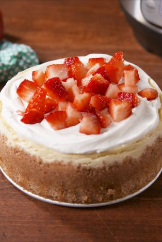 instant pot cheesecake new york style with whipped cream and strawberries on top