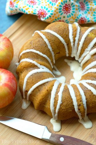 pumpkin apple bundt cake with white icing drizzled on top on a wooden board with two apples, a knife and a multi patterned napkin in the background