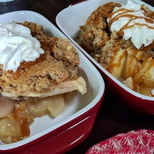 Mom's delicious apple crisp with whipped cream in two red serving dishes