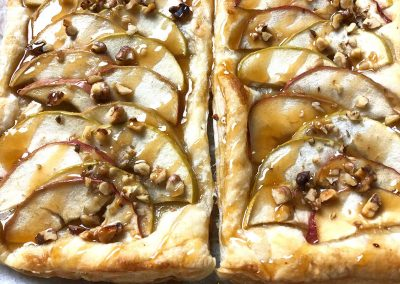 two sections of french apple tart side by side with caramel sauce