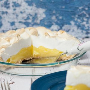 lemon meringue pie with slice removed and pie server with a slice of pie in foreground on blue plate