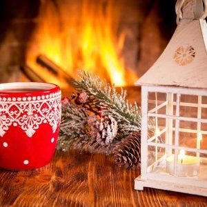 red mug with lace design, white lantern on wooden table in front of fireplace and pine cones and pine branches
