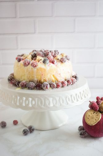 cheesecake with cranberries on white cake plate with white brick background and red & gold ornament to the left